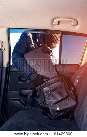 Robber in black mask breaking into a car and stealing laptop computer.