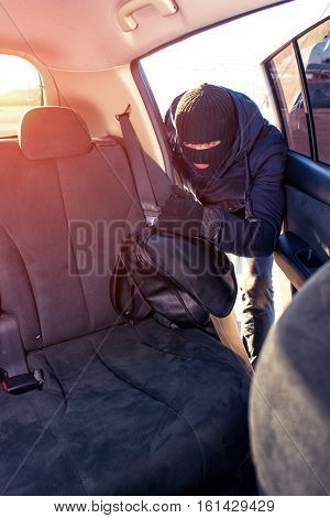 Unrecognizable man in black robbery mask stealing bag from car. Thief taking handbag from back seat.