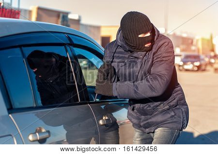 Car theft male thief in black robbery mask breaking into car using screwdriver.