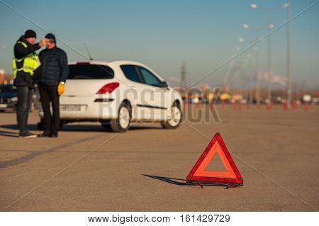 Male Driver And Car Technician Next To Broken Auto