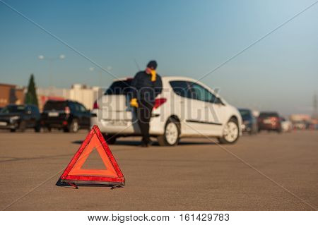 Car breakdown: young man calling to car assistance after accident. Red emergency warning sign.