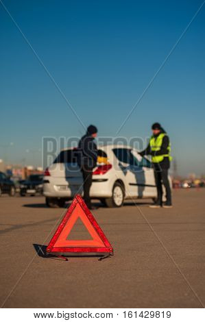 Car assistance technician checking documents with driver. auto breakdown. Red triangle warning sign.