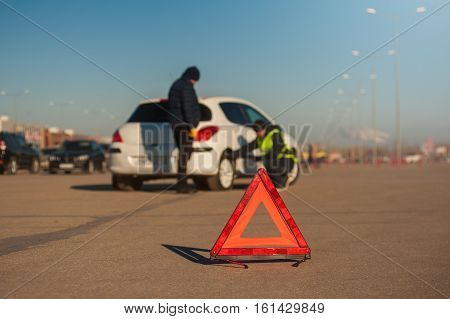 Car assisstance technician checking wheel. Auto breakdown male driver staying next to car. Red triangle warning sign foreground.