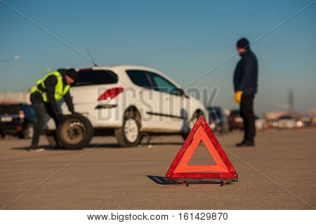 Car assistance repairman changing spare wheel on parking. Male driver with technician after breakdown. Red triangle emergency sign.