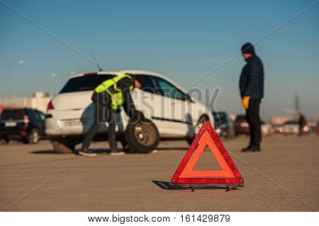 Male driver staying next to car after breakdown. Car assistance technician changing wheel on parking outdoors. Red triangle warning sign.