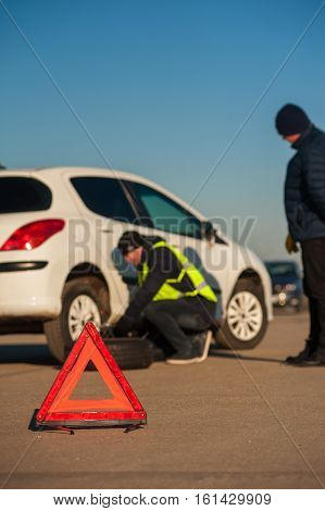 Car repairman changing flat tire after breakdown. Male driver standing next to broken car. Red triangle warning sign foreground.