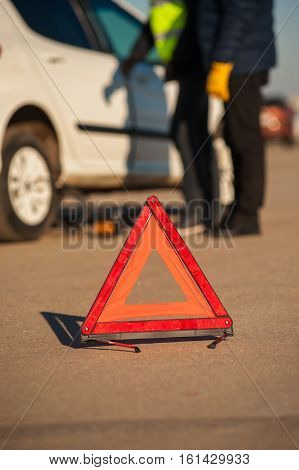 Red triangle warning sign on the background of car technician and driver checking auto. Fall or winter sunny day.