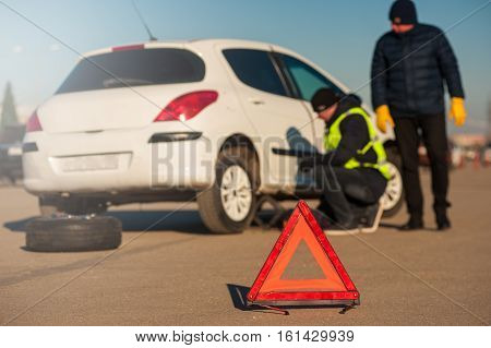 Car assistance technician repairing auto after breakdown. Male driver standing next to car. Red emergency sign foreground. Winter or fall sunny day