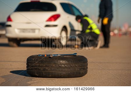 Wrench and spare wheel on the background of car assistance technician and male driver. Auto breakdown outdoors.