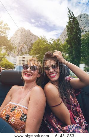 Two girls having fun at the back seat of convertible. Vintage filter applied.