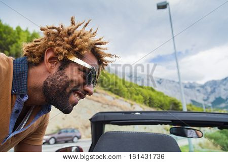 Young happy black man with dread locks wearing sunglasses leaning over convertible car.
