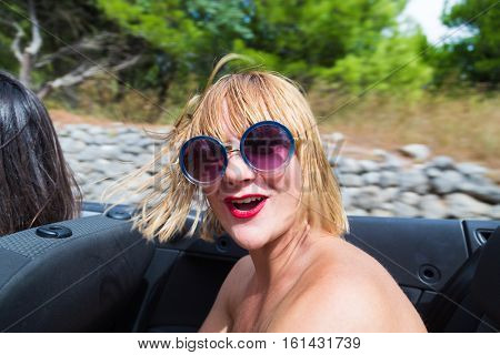 Happy blonde wearing sunglasses sitting and smiling in the back seat of convertible car.