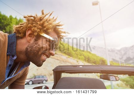Young happy black man with dread locks wearing sunglasses leaning over convertible car. Sun effect applied.
