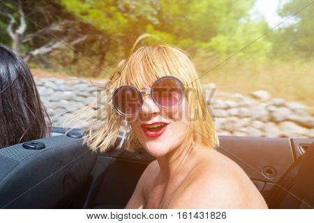 Happy brunette girl sitting and smiling in the back seat of convertible car. Sun effect applied.