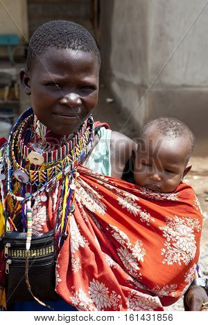 BISIL, KENYA-DECEMBER 7, 2010: Portrait of unidentified Maasai woman and child in a rural village in Kenya