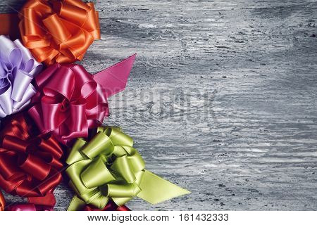 some satin gift ribbon bows of different colors on a rustic wooden surface, with a negative space