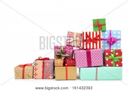 closeup of a pile of gifts wrapped in nice papers and tied with ribbons of different colors on a white background
