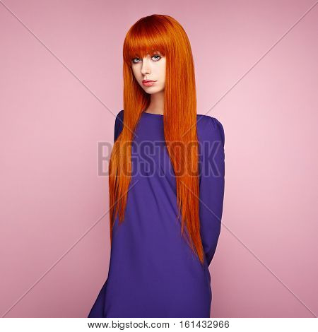 Portrait of beautiful woman with red hair. Colored long haircut. Perfect make-up. Girl in elegant violet dress. Red wig. Fashion photo