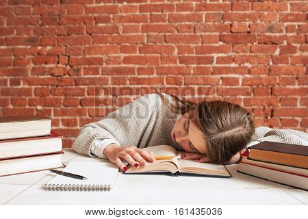 Tired student sleeping on book at library, free space. Exhausted of studying girl napping while reading tutorial material, copy space on brick wall background. Education, exams concept