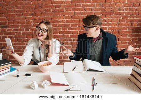 Girl taking selfie while study, her partner at a loss of her behavior. Having fun at lesson, teamwork, education, beauty and nerd concept