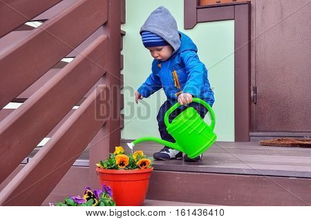 the little boy standing on a porch waters flowers from a watering can