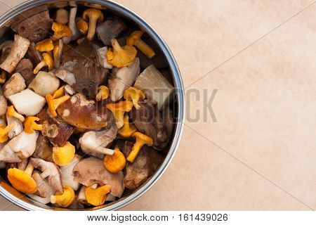 Raw Fresh Edible Mushrooms Chanterelles And Clean Cut Porcini In Large Metal Kitchen Pot Pan On Beige Brown Background. Top View And Copyspace.