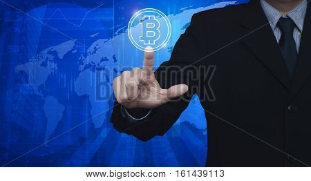 Businessman pressing bit coin icon over world map and city background Elements of this image furnished by NASA