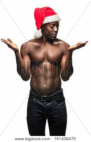 Muscular black shirtless young man in Santa Claus hat standing on white studio background and showing something