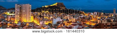 Costa Blanca Spain. Aerial night view of Alicante - summer resort of Costa Blanca region in Spain. Old city center with harbor illumination. Santa Barbara Castle located on Mount Benacantil