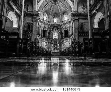 ELCHE SPAIN - JULY 6 2015: Inside the Basilica Menor de Santa Maria. Main altar with reflection in the floor. Black and white interior in Elche Spain