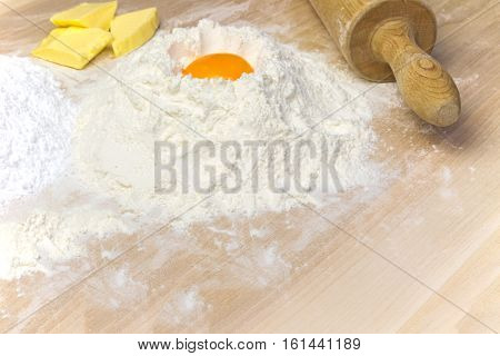 Preparation for baking - The pile of flour with egg yolk on the top pile of sugar butter and wooden rolling pin are on the wooden desk. Free place for your text is on the lower edge of the photo.