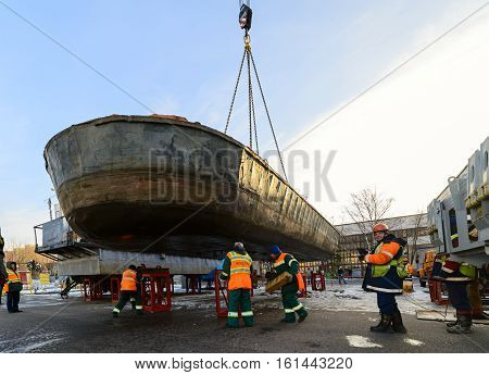 MOSCOW, RUSSIA - NOVEMBER 11, 2016: State Unitary Enterprise Mosvodostok performs recovery vessels on coastal winter parking. Dockers set barge on metal supports.