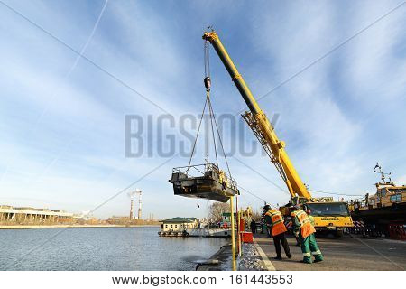 MOSCOW, RUSSIA - NOVEMBER 11, 2016: State Unitary Enterprise Mosvodostok performs recovery vessels on coastal winter parking. Car crane lifts the ship.
