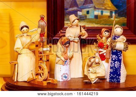 folk style traditional handmade figures made from natural materials doing chores and crafts
