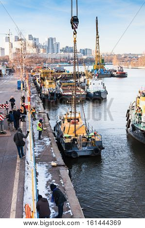 MOSCOW, RUSSIA - NOVEMBER 11, 2016: State Unitary Enterprise Mosvodostok performs recovery vessels on coastal winter parking. The ship rises out of the water with the help of truck crane.