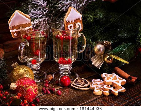 Two glasses of grog, decoration Christmas cookies in shape of houses. Christmas balls and Christmas tree in background.