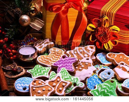 Christmas celebration for family. Christmas gift box under and lots of colored gingerbread Christmas cookies in foreground.