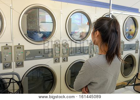 Asian woman waiting for laundry machine in public laundromat.