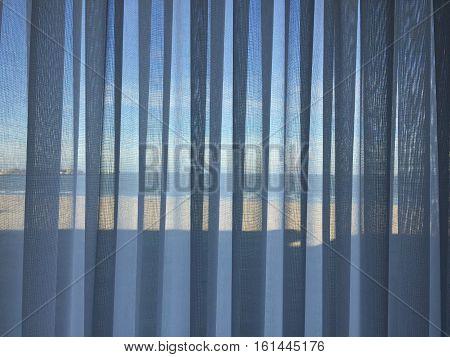Beach view behind blue curtain glass window
