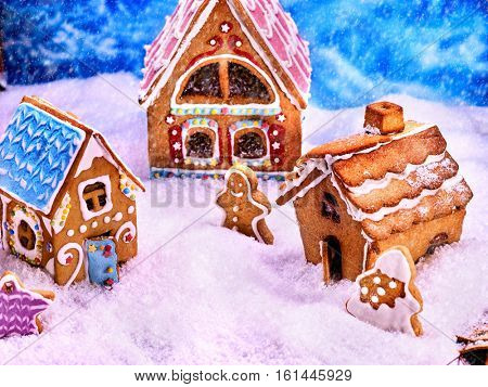 Three colorful Christmas gingerbread house, standing in semicircle surrounded by gingerbread cookie man, Christmas trees and gingerbread cookie stars.