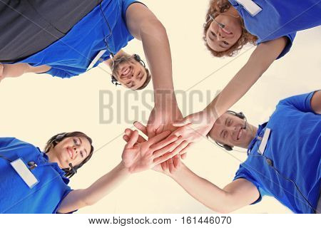 Team of technical support dispatchers holding hands together