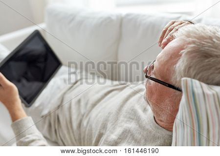 technology, old age, people and lifestyle concept - senior man with tablet pc computer lying on sofa at home