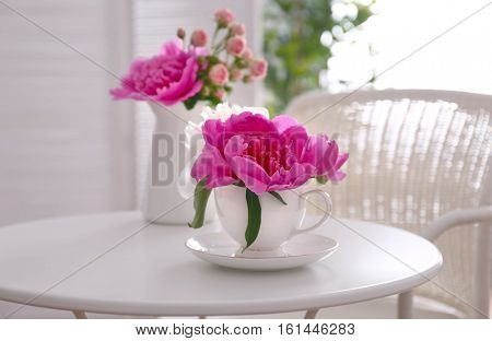 Flower bouquet of peonies in cup on table