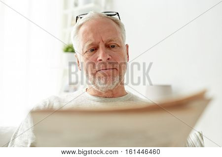 information, people, and mass media concept - close up of senior man reading newspaper at home
