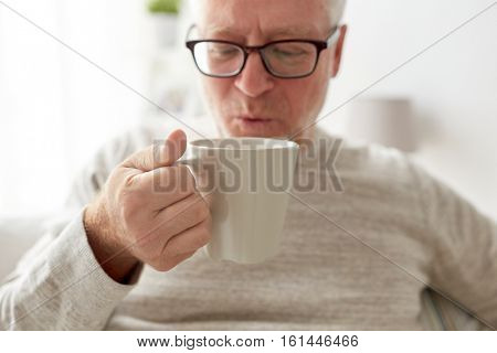 old age, drink and people concept - happy senior man drinking tea or coffee at home