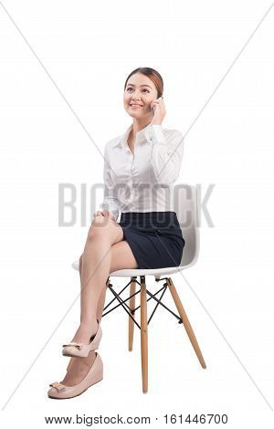 Full Length Portrait Of Beautiful Young Asian Business Woman Sitting On A Chair Listening To Mobile
