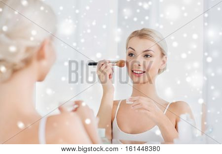beauty, make up, cosmetics, morning and people concept - smiling young woman makeup brush and powder foundation looking to mirror at home bathroom over snow