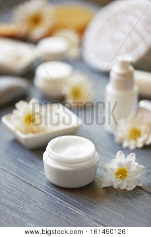 Spa concept. Nourishing cream and daisy flowers on grey wooden table