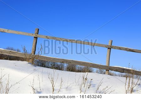 wooden fence on slope in winter meadow