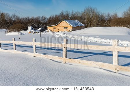 winter scene with wooden fence on rural farm